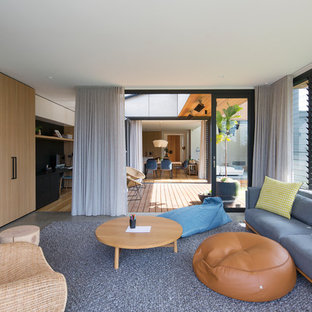This is an example of a mid-sized contemporary open concept family room in Sydney with a wall-mounted tv and grey floor.