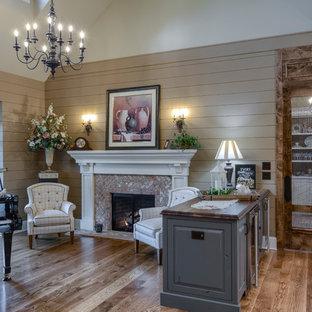 Modelo de sala de estar con rincón musical tipo loft, campestre, grande, sin televisor, con suelo de madera en tonos medios, suelo marrón, paredes beige, chimenea tradicional y marco de chimenea de ladrillo