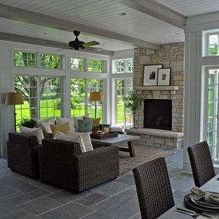 Ispirazione per un soggiorno classico di medie dimensioni e aperto con pavimento in ardesia, camino classico, cornice del camino in pietra e pavimento blu
