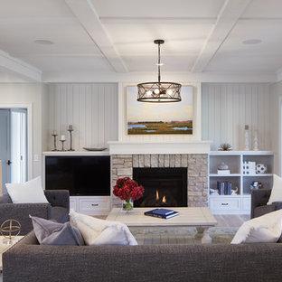 Imagen de sala de estar abierta, de estilo de casa de campo, de tamaño medio, con paredes blancas, suelo de madera clara, chimenea tradicional, marco de chimenea de piedra, pared multimedia y suelo marrón