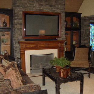 Photo of a mid-sized mediterranean open concept family room in San Luis Obispo with a library, beige walls, carpet, a standard fireplace, a stone fireplace surround and a built-in media wall.