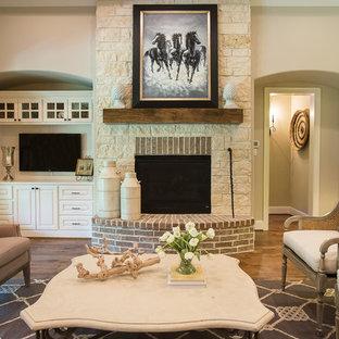Aménagement d'une salle de séjour classique avec un mur beige, une cheminée standard, un téléviseur fixé au mur, un sol en bois brun et un manteau de cheminée en pierre.