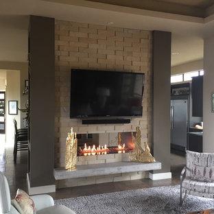 Idee per un soggiorno contemporaneo di medie dimensioni e aperto con pareti grigie, pavimento in ardesia, camino bifacciale, cornice del camino in pietra e TV a parete
