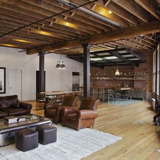 Industriell inredning av ett stort allrum med öppen planlösning, med flerfärgade väggar och ljust trägolv