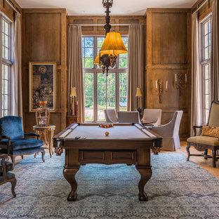 Elegant enclosed medium tone wood floor and beige floor game room photo in Miami with brown walls