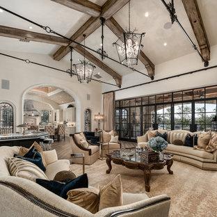 Idée de décoration pour une très grande salle de séjour ouverte avec un bar de salon, un mur blanc, un sol en bois brun, une cheminée standard, un manteau de cheminée en pierre, un téléviseur fixé au mur et un sol marron.