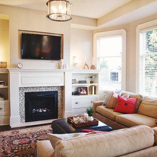 Foto de sala de estar cerrada, marinera, con paredes beige, suelo de madera oscura, chimenea tradicional, marco de chimenea de baldosas y/o azulejos y televisor colgado en la pared