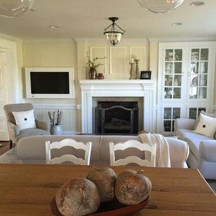 Immagine di un piccolo soggiorno country aperto con pavimento in legno massello medio, cornice del camino in cemento, TV a parete, pareti gialle e camino classico