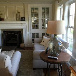Diseño de sala de estar abierta, campestre, pequeña, con suelo de madera en tonos medios, televisor colgado en la pared, paredes amarillas, chimenea tradicional y marco de chimenea de yeso