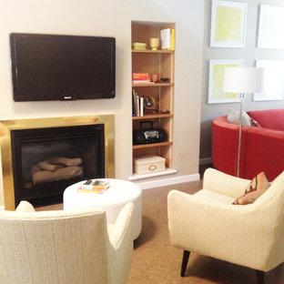 Foto de sala de estar moderna, pequeña, con paredes beige, suelo de corcho, chimenea tradicional, marco de chimenea de metal y televisor colgado en la pared
