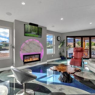Mittelgroßes, Offenes Modernes Wohnzimmer mit grauer Wandfarbe, Betonboden, Kaminsims aus Metall, Wand-TV und buntem Boden in Denver