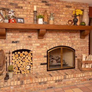 シカゴの中サイズのラスティックスタイルのおしゃれな独立型ファミリールーム (ベージュの壁、テラコッタタイルの床、標準型暖炉、レンガの暖炉まわり、テレビなし、赤い床) の写真