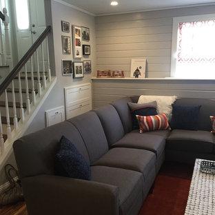 Esempio di un soggiorno chic di medie dimensioni e aperto con pareti grigie, pavimento in legno massello medio, nessun camino, TV a parete, pavimento marrone e sala giochi