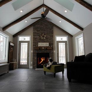 Diseño de sala de estar abierta, romántica, de tamaño medio, sin televisor, con paredes grises, suelo de baldosas de porcelana, chimenea tradicional y marco de chimenea de piedra