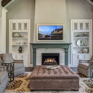 Family room - mid-sized traditional open concept dark wood floor and brown floor family room idea in Columbus with gray walls, a standard fireplace, a stone fireplace and a concealed tv