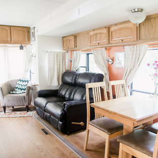 Imagen de sala de estar abierta, ecléctica, pequeña, con parades naranjas y televisor retractable