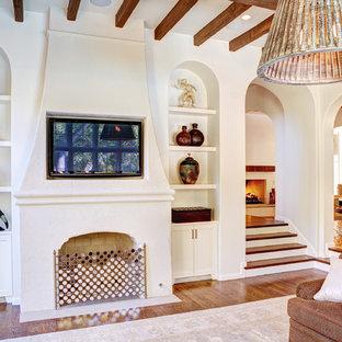 Imagen de sala de estar abierta, mediterránea, grande, con paredes blancas, suelo de madera en tonos medios, chimenea tradicional, televisor colgado en la pared y marco de chimenea de yeso