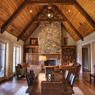Diseño de sala de estar abierta, clásica, grande, sin televisor, con paredes beige, suelo de madera en tonos medios, chimenea tradicional y marco de chimenea de piedra