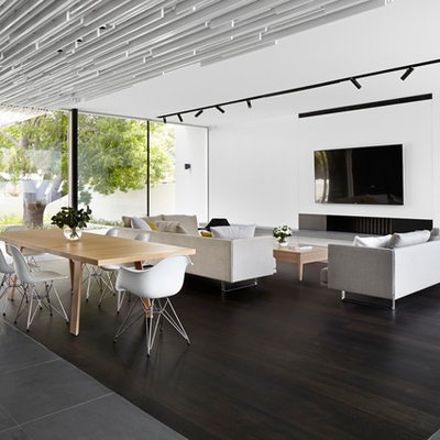 Example of a large trendy open concept dark wood floor family room design in Perth with white walls, a standard fireplace, a plaster fireplace and a wall-mounted tv