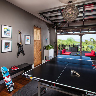 Game room - large contemporary enclosed medium tone wood floor game room idea in Orange County with beige walls, no fireplace and a wall-mounted tv