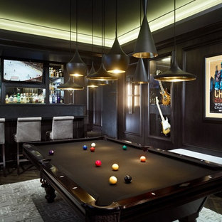 This is an example of a contemporary family and games room in Chicago with a home bar, black walls and a wall mounted tv.