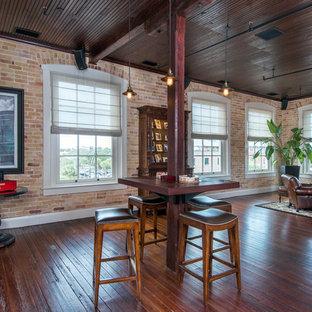 タンパのトラディショナルスタイルのおしゃれなファミリールーム (ホームバー、赤い壁、濃色無垢フローリング、茶色い床) の写真