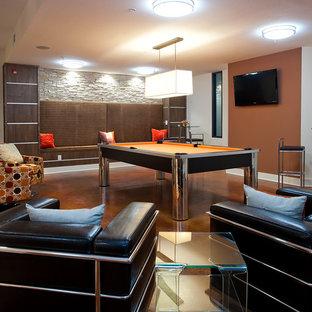 Exemple d'une grand salle de séjour tendance ouverte avec salle de jeu, un mur orange, béton au sol, un téléviseur fixé au mur, aucune cheminée et un sol marron.