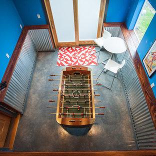 シアトルの中サイズのインダストリアルスタイルのおしゃれな独立型ファミリールーム (ゲームルーム、青い壁、コンクリートの床、暖炉なし、壁掛け型テレビ、グレーの床) の写真