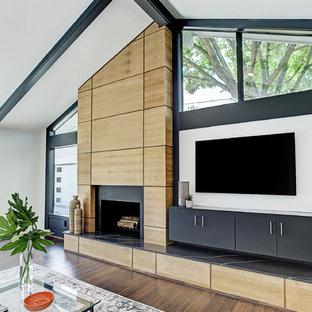 ヒューストンのミッドセンチュリースタイルのおしゃれなファミリールーム (白い壁、竹フローリング、標準型暖炉、木材の暖炉まわり、壁掛け型テレビ、茶色い床) の写真