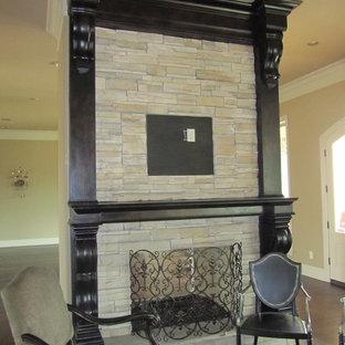 ニューオリンズの中サイズのトラディショナルスタイルのおしゃれな独立型ファミリールーム (ベージュの壁、濃色無垢フローリング、標準型暖炉、石材の暖炉まわり、テレビなし、茶色い床) の写真