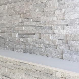 Ejemplo de sala de estar moderna, pequeña, con paredes grises, moqueta, chimenea tradicional y marco de chimenea de piedra