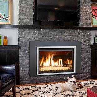 Modelo de sala de estar con barra de bar cerrada, actual, de tamaño medio, con paredes azules, suelo de madera en tonos medios, marco de chimenea de piedra, chimenea tradicional y televisor colgado en la pared