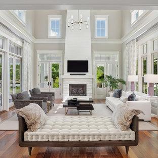 Großes, Offenes Modernes Wohnzimmer mit grauer Wandfarbe, dunklem Holzboden, Kamin, Kaminumrandung aus Holzdielen, Wand-TV, braunem Boden und gewölbter Decke in Charleston