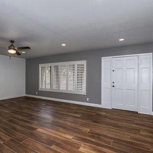 フェニックスの大きいコンテンポラリースタイルのおしゃれなファミリールーム (グレーの壁、磁器タイルの床、標準型暖炉、レンガの暖炉まわり、壁掛け型テレビ) の写真