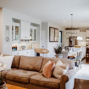 Modelo de sala de estar abierta, campestre, de tamaño medio, con paredes beige, suelo de madera oscura, chimenea tradicional, marco de chimenea de yeso, televisor retractable y suelo marrón