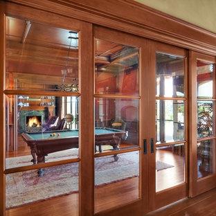 サンディエゴの巨大なトラディショナルスタイルのおしゃれな独立型ファミリールーム (ゲームルーム、赤い壁、無垢フローリング、標準型暖炉、タイルの暖炉まわり、テレビなし、茶色い床) の写真