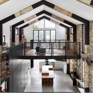 Imagen de sala de estar tipo loft, urbana, de tamaño medio, con paredes multicolor, suelo de cemento, estufa de leña, marco de chimenea de hormigón y televisor colgado en la pared