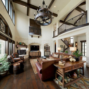 Large mediterranean open concept family room in Houston with dark hardwood floors, a corner fireplace and a stone fireplace surround.