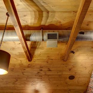 Foto di un soggiorno industriale di medie dimensioni e stile loft con angolo bar, pareti grigie, parquet scuro, TV a parete, pavimento marrone e nessun camino