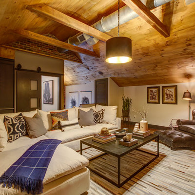 Inspiration for a mid-sized rustic loft-style dark wood floor and brown floor family room remodel in Raleigh with a bar, gray walls, a wall-mounted tv and no fireplace