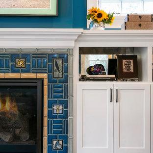 ミネアポリスの中サイズのエクレクティックスタイルのおしゃれなファミリールーム (青い壁、淡色無垢フローリング、標準型暖炉、タイルの暖炉まわり、壁掛け型テレビ、黄色い床) の写真