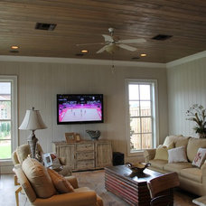 Tropical Family Room by Pelican Builders Group