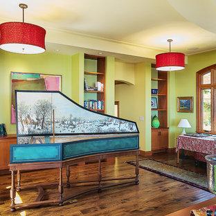 Cette photo montre une salle de séjour éclectique de taille moyenne et ouverte avec une salle de musique, un mur vert, un sol en bois foncé, aucune cheminée, aucun téléviseur et un sol marron.