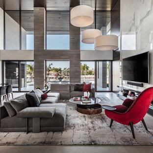 Aménagement d'une très grande salle de séjour contemporaine ouverte avec un sol en carrelage de porcelaine, un téléviseur fixé au mur, un mur blanc et un sol gris.