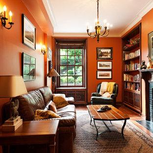 Idée de décoration pour une salle de séjour avec une bibliothèque ou un coin lecture tradition avec un mur orange, une cheminée standard et aucun téléviseur.