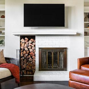 Cette image montre une petite salle de séjour traditionnelle fermée avec un mur beige, un sol en bois foncé, une cheminée standard, un manteau de cheminée en brique et un téléviseur fixé au mur.