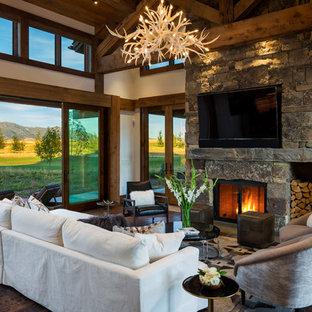 Diseño de sala de estar abierta, rural, con suelo de madera oscura, chimenea tradicional y televisor colgado en la pared