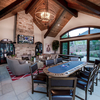 Example of a huge mountain style enclosed limestone floor and white floor game room design in Denver with a wall-mounted tv, beige walls, a standard fireplace and a stone fireplace