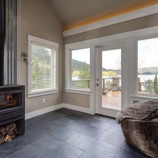 シアトルのビーチスタイルのおしゃれな独立型ファミリールーム (ベージュの壁、スレートの床、薪ストーブ、金属の暖炉まわり、黒い床) の写真