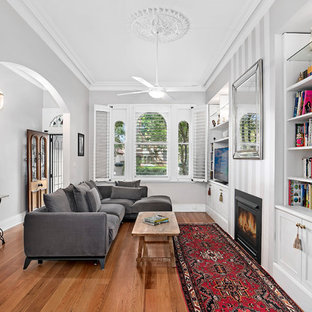 Inspiration for a victorian open concept family room in Sydney with white walls, medium hardwood floors, a standard fireplace, a built-in media wall and brown floor.